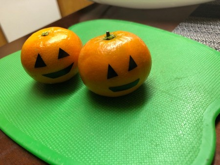 Making a Halloween Fruit Display - Jack 'o Lantern tangerines with tape cut for eyes and mouth