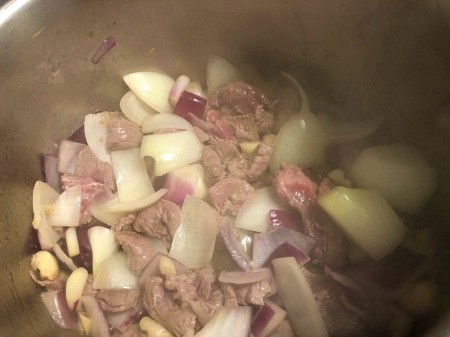 cooking meat, onions & garlic in pan