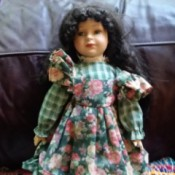 Identifying a Porcelain Doll - doll wearing a plaid dress with a floral apron