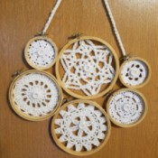 Embroidery Hoop Doily Wall Decoration - glue on the buttons and then arrange the hoops in a pleasing way and glue, add a chained hanger