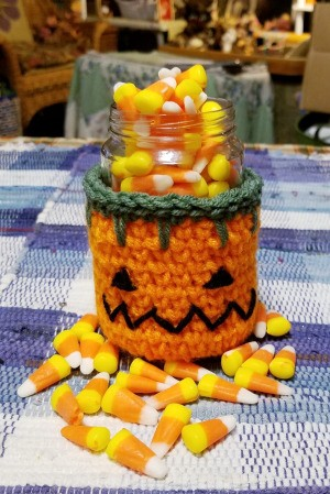 Crocheted Pumpkin Candy Jar Cover - pumpkin candy jar filled with candy corn, with some scattered around the jar on the table