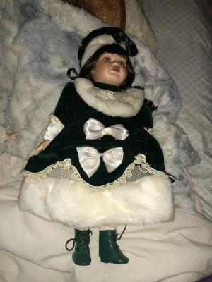 Identifying Porcelain Dolls - doll wearing a dark green velvet dress and matching hat trimmed in white fur
