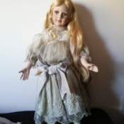 Identifying a Porcelain Doll - doll in old style dress with embroidery on the bottom
