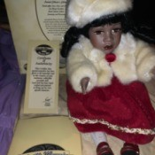 Value of a Collectible Memories Musical Doll - doll wearing a red dress and white fur hat and jacket, sitting next to its box