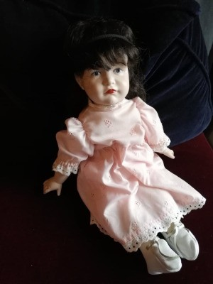 Value of a Reproduction Kammer & Reinhardt Porcelain Doll - dark haired doll wearing a pink dress with eyelet lace trim