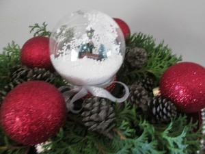 Budget Friendly Snow Globe - filled globe surrounded by red Christmas ornaments, pine cones, and greenery