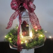 Making A Lantern Part Of Your Holiday Decor - ornament filled white lantern on a display stand surrounded by greenery, pine cones, and fairy lights