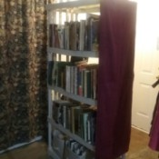An open shelf with a burgundy panel on the end.