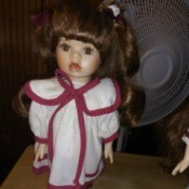 Value of a Collector's Choice Porcelain Doll - doll wearing a long white dress with red trim