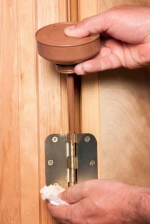 Door hinge getting oil applied.