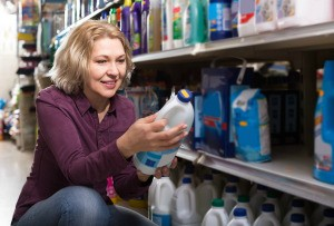 A woman reading a bottle of bleach in a store.