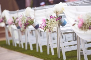 Wedding flowers in small buckets hanging off chairs.