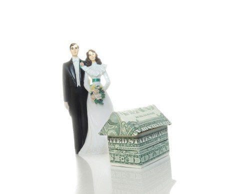 Bride and groom cake topper next to money folded into a house shape.