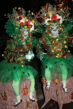 Two forest nymphs with light up wings sitting on stumps.