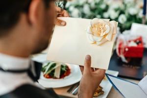 Groom looking at a wedding card.
