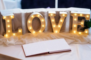 Wedding guest book with letter lights spelling LOVE.