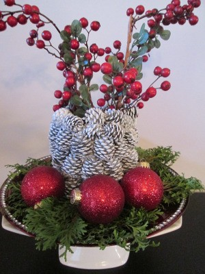 Pine Cone Vase - vase surrounded by greenery and red ornaments and filled with faux berry srays
