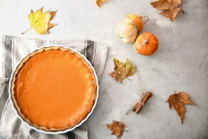 Pumpkin pie with fall leaves and gords.