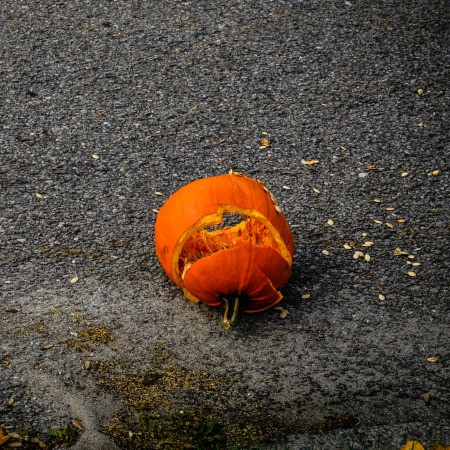 A carved pumpkin Jack-'o-lantern smashed on the pavement.