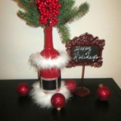 Santa Vase And Lamp - greenery added to bottle to use as a vase, displayed with a sign saying Happy Holidays and some Christmas ornaments