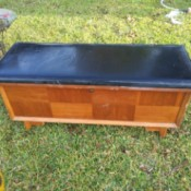 Value of a Lane Sweetheart Cedar Chest - chest with black upholstered top and 8 veneer panels on the front