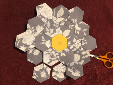 English Paper Pieced Flower Pillow - keep working around the piece stitching hexagons in place