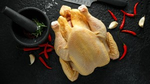 A whole chicken being prepared for cooking.