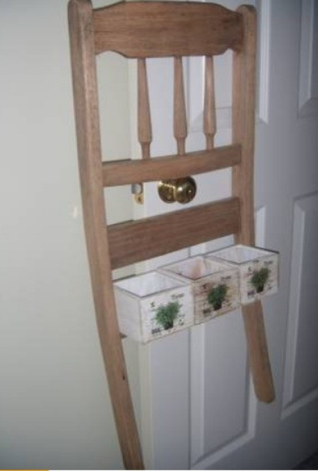 A chair back used as a planter hanger.