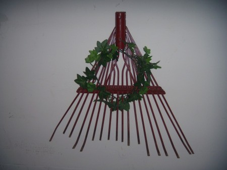 A rake head with a decorative wreath.