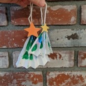 Folded Christmas Tree Ornament - hand holding the ornaments with fireplace bricks in the background