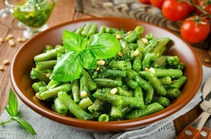 A green bean side dish served with pine nuts.