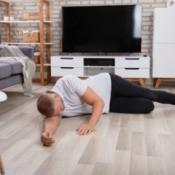 A man who has fainted on a living room floor.