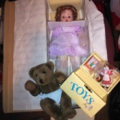 Value of an Ashton Drake Porcelain Doll - doll in the box, with teddy and toy box