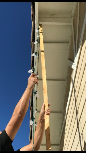 Using a stick to hang Christmas lights on the house.
