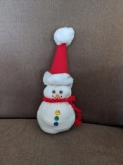 No-Sew Christmas Sock Snowman - finished snowman on a beige couch
