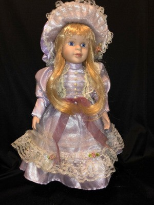 Identifying a Porcelain Doll - doll wearing a lace and satin dress and matching hat