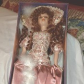 Value of Ashley Belle Dolls - doll wearing a dark pink satin dress in the box