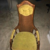 Value of a Jack Brandt Chair - wooden cane back chair with upholstered headrest, part of the arms, and a cushion