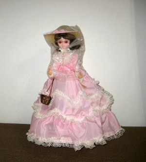 Information on a Brinn Plastic and Fabric Doll - doll wearing long full pink dress with white lace trim