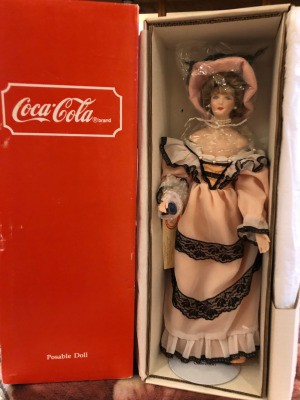 Value of a Coca Cola Heritage Doll - doll in box wearing a Victorian era dress and hat