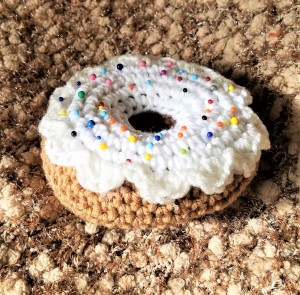 Crocheted Donut Pincushion - icing in place with pins randomly stuck in place