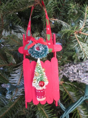 Popsicle Stick Sled - red sled with wreath and tree decorations, hanging on the Christmas tree