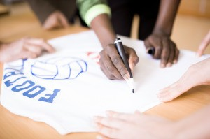 Writing an autograph on a football t-shirt.