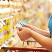 A woman using coupons when grocery shopping.