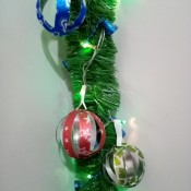 Recycled Plastic Bottle Christmas Balls - finished balls hanging on a lighted piece of garland