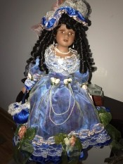 Value of a Crimson Collection Porcelain Doll - doll wearing a blue satin dress with white lace