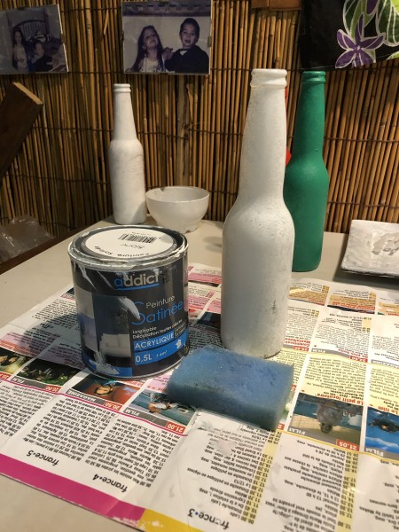 Recycled Bottle Holly Leaf  Candlestick Holder - cleaned bottles primed with white paint, can of paint and a sponge in the foreground