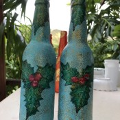 Recycled Bottle Holly Leaf Candlestick Holder - two blue bottles with holly leaves painted on to use as candleholders