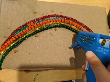 Rainbow Name Room Decor - child glueing pipe cleaners to cardboard with hot glue gun