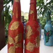 Recycled Bottle Gold Leaf Candlestick Holders - two red bottles with gold leaf elements